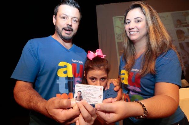 #Pracegover Foto: na imagem há três pessoas. Uma criança, um homem e uma mulher