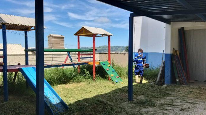 #Pracegover Foto: na imagem há brinquedos, estrutura metálica e um homem roçando o local com mato