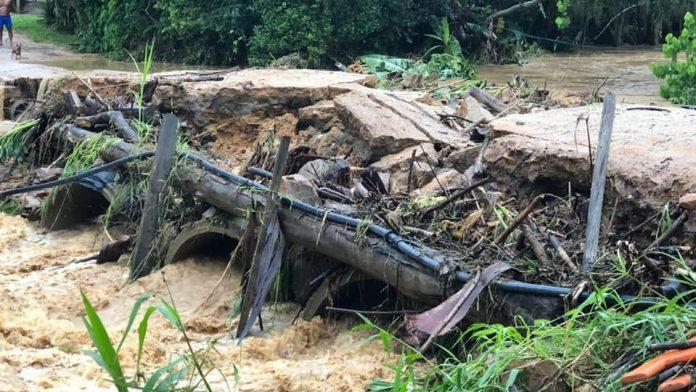 #Pracegover Na foto, tubulações para passagem do rio sob a estrada estão expostas e cobertas por galho