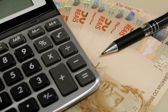 #Pracegover Foto: na imagem há uma calculadora, caneta e cédulas de 50 reais