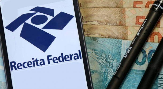 #Pracegover Na foto, a tela de um celular com a página da Receita Federal, uma caneta e dinheiro