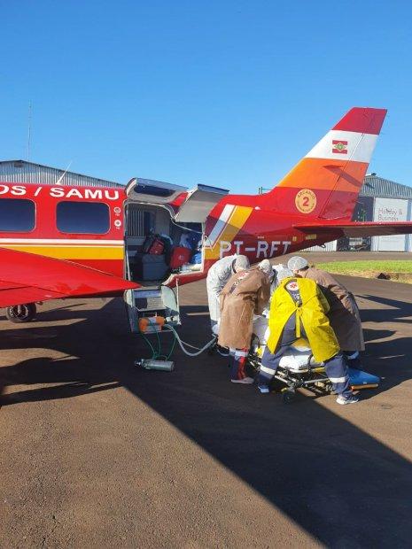 #Pracegover Na foto, Bombeiros preparam pacientes antes da transferência feita pela aeronave