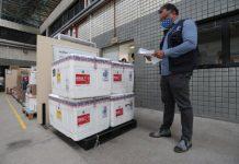 #Pracegover Na foto, caixas com a vacina e um profissional fazendo a conferência durante a chegada.