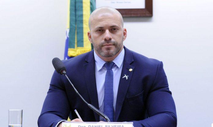 #Pracegover Foto: na imagem há um homem de terno azul, camisa branca e gravata azul. Há um microfone, uma bandeira do Brasil e um quadro