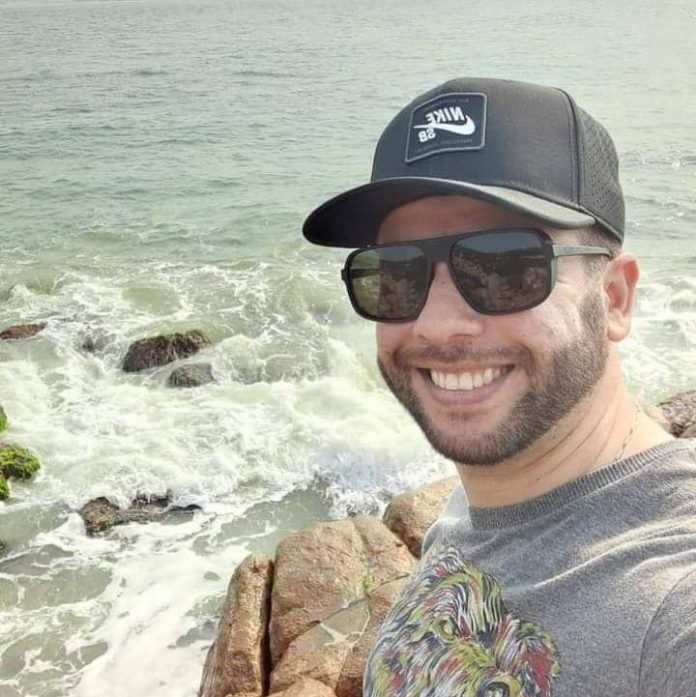 #Pracegover Foto: na imagem há um homem de boné, óculos escuro, camiseta cinza e ele está sorridente