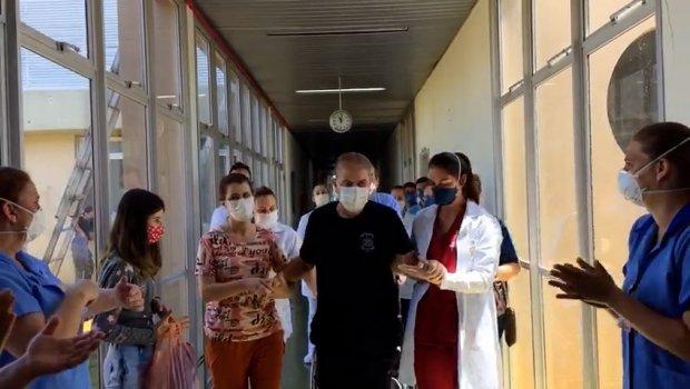 #Pracegover Na foto, Luciano Turatto saindo do hospital com auxílio das enfermeiras e a família