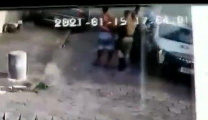#Pracegover Foto: na imagem há um homem sem camisa e um policia, um veículo e a viatura da PM