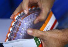 #Pracegover Foto: na imagem há duas mãos e muitas doses de vacinas