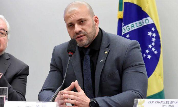 #Pracegover Foto: na imagem há um homem de terno escuro, sentado e uma bandeira do Brasil