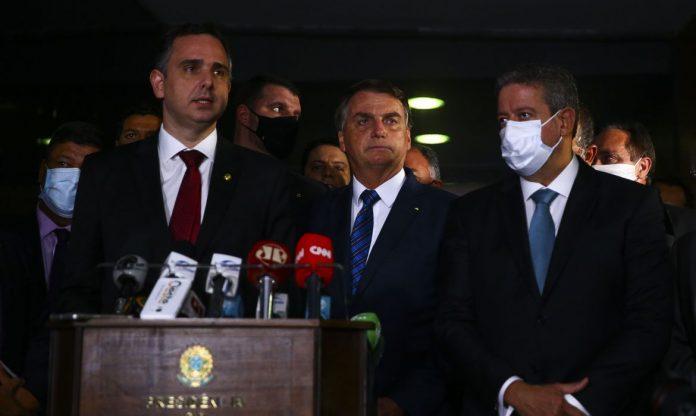 #Pracegover Foto: na imagem há alguns homens de terno e microfones