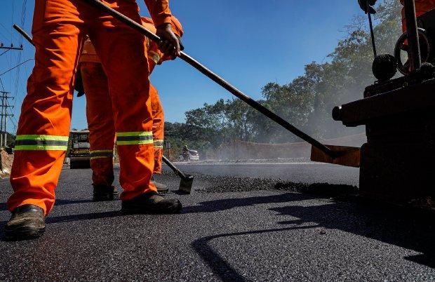 #Pracegover Na foto, um homem trabalhando no asfaltamento de uma rua