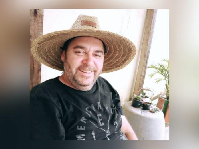 #Pracegover Foto: na imagem há um homem sorrindente, de camiseta preta, chapéu. Próximo a ele há um celular e alguns plantas