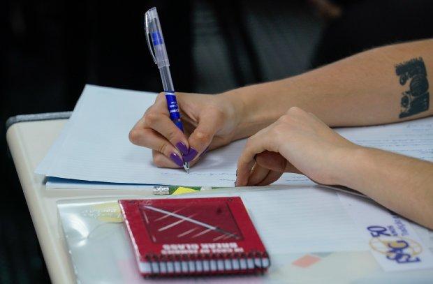 #Pracegover Foto: na imagem há dois braços, duas mãos, uma caneta, um bloco de notas e um caderno