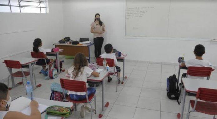 #Pracegover Foto: na imagem há crianças, uma mulher, carteiras, cadeiras, mesa e um quadro