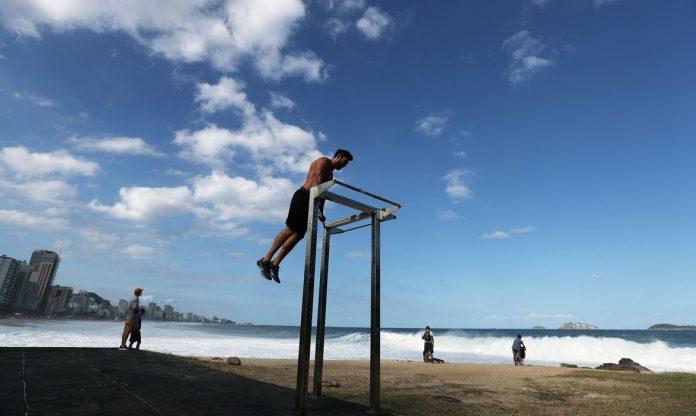 #Pracegover Foto: na imagem há uma pessoa fazendo exercício e outras olhando para o mar