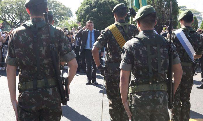 #Pracegover Foto: na imagem há vários homens fardados e um de terno