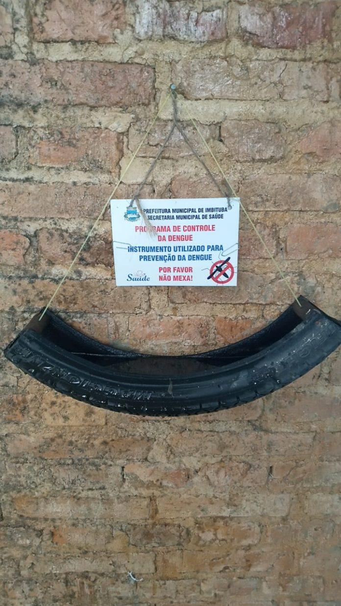 #Pracegover Foto: na imagem há uma metade de um pneu, uma parede e um cartaz