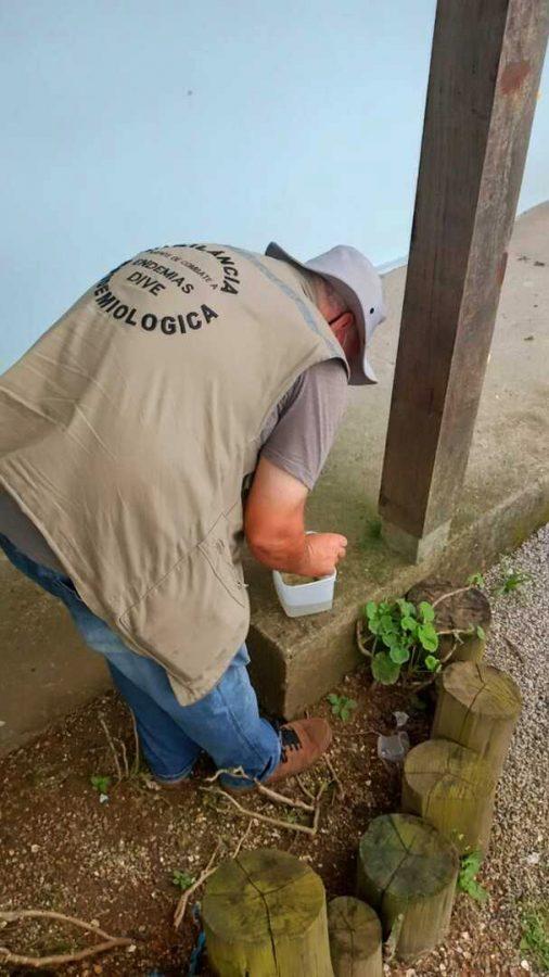 #Pracegover Foto: na imagem há um homem de chapéu, um recipiente e uma calçada