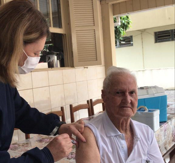 #Pracegover Foto: na imagem há um idoso e uma mulher de máscara aplicando vacina no homem. Há cadeiras, mesa e janela