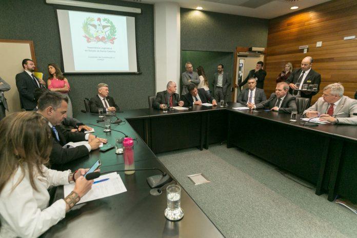 #Pracegover Foto: na imagem há uma mesa, copo e várias pessoas em reunião