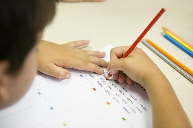 #Pracegover Foto: na imagem há uma criança, alguns lápis de cor e uma folha