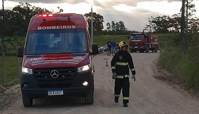 #Pracegover Foto: na imagem há carros do Corpo de Bombeiros, profissionais de Bombeiros, populares, árvores, um caminhão guincho e uma estrada