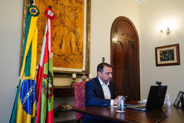 #Pracgover Foto: na imagem há um homem de terno, bandeiras, um copo de água, notebook, mesa, cadeira e um quadro