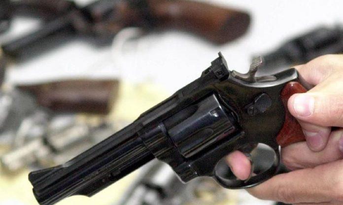#Pracegover Na foto, um homem segura uma arma de fogo