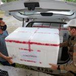#pracegover Na foto, dois homens colocando caixas de vacina em um carro para a entrega
