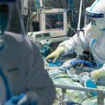 #pracegover Na foto, um profissional da saúde cuidando de um paciente internado na UTI