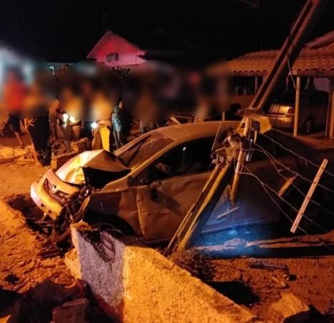 #Pracegover Na foto, um carro destruído após colidir em um muro e poste de energia