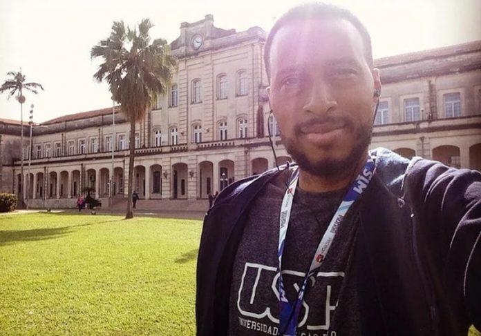#Pracegover Foto: na imagem há um homem e ao fundo um prédio de universidade e um gramado
