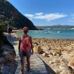 #pracegover uma mulher caminha sobre um deck entre um morro e as pedras na beira do mar