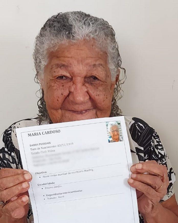 #Pracegover Na foto, Dona Maria segurando o currículo que a família fez