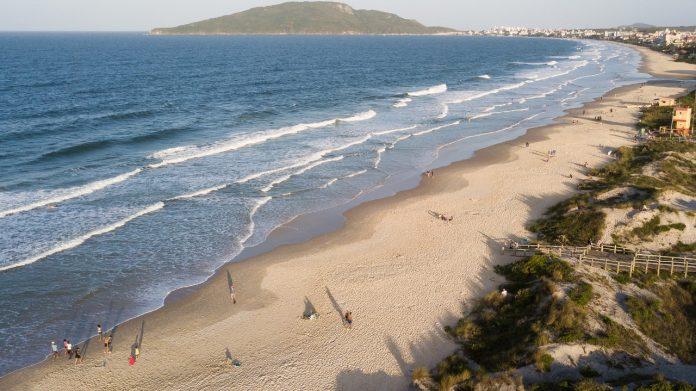 #Pracegover Foto: na imagem há o mar, a areia, árvores e pessoas