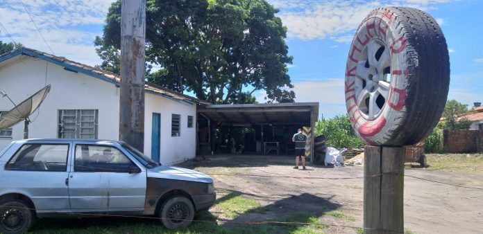 #Pracegover Foto: na imagem há uma residência, um carro, um homem e um pneu em frente do terreno