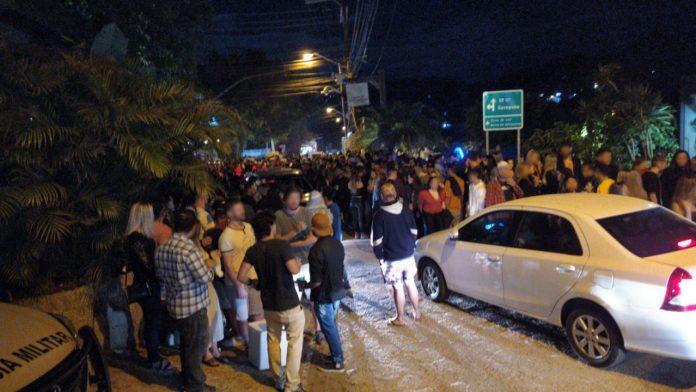 #Pracegover Foto: na imagem há inumeras pessoas aglomeradas e um carro