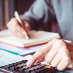 #Pracegover Foto: na imagem há uma pessoa fazendo contas e uma calculadora e escrevendo em um caderno