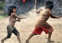 #Pracegover Foto: na imagem há duas crianças indígenas sem camisa e de bermuda brincando