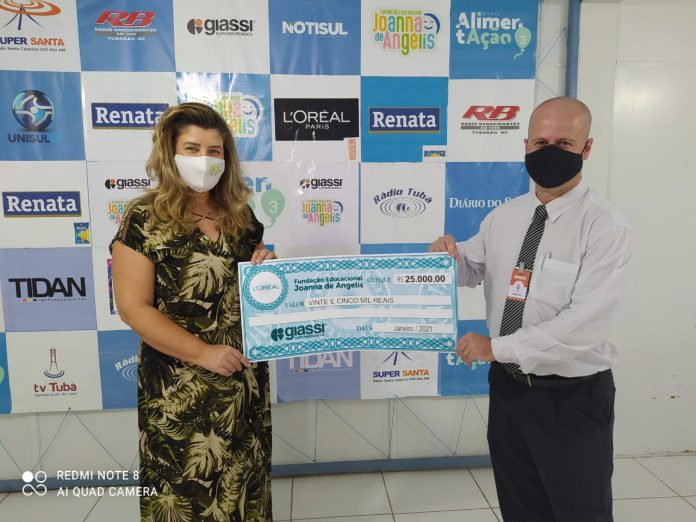 #Pracegover Foto: na imagem há duas pessoas segurando um cheque simbólico