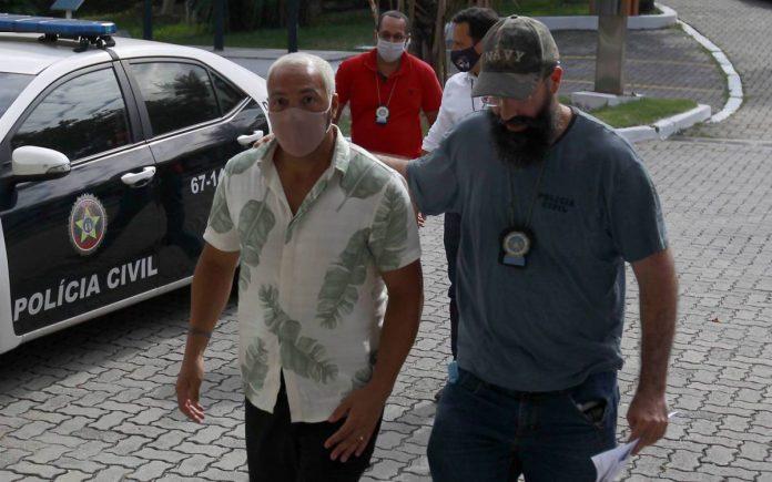 #pracegover Na foto, cantor Belo sendo acompanhado por um policial