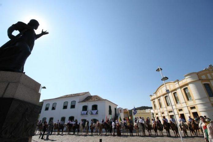 #Pracegover Foto: na imagem há casas, cavalos e pessoas