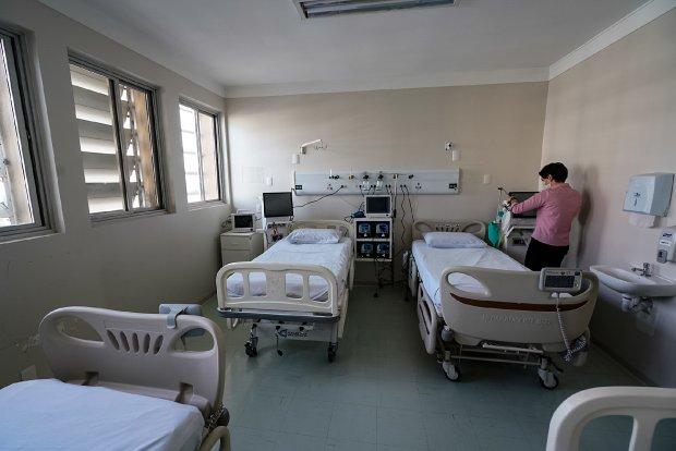 #Pracegover Foto: na imagem há uma pessoa em pé e quatro leitos de enfermaria