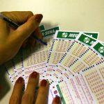 #Pracegover Na foto, uma mulher marcando números em bilhete de loteria