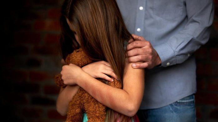 #Pracegover Na foto, uma menina com idade aproximada de 8 anos segurando um urso de pelúcia e um homem atrás com mãos no ombro da menina