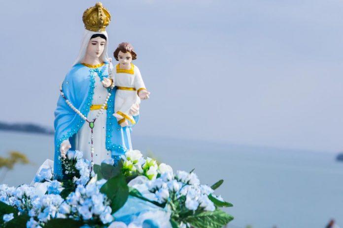 #Pracegover Foto: na imagem há a Nossa Senhora dos Navegantes com uma criança no colo, um terço e flores