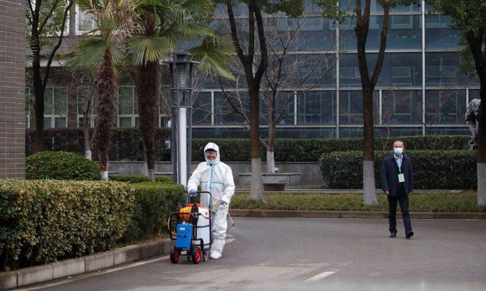 #Pracegover Na foto, um profissional higienizando as ruas em cidade da China