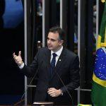 #Pracegover Foto: na imagem há um homem de terno, gesticulando com as mãos, microfones e a bandeira do Brasil