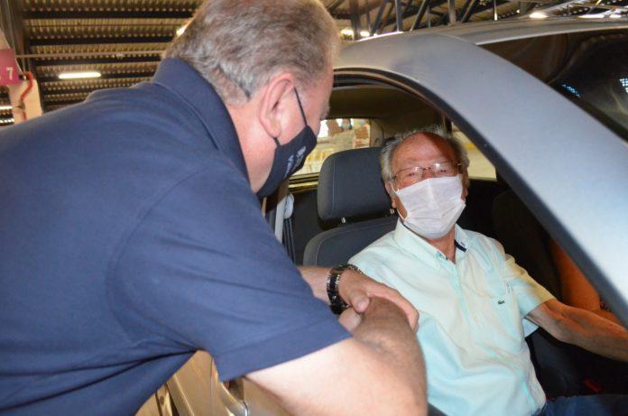 #Pracegover Foto: na imagem há o padre Raimundo dentro de um carro e o prefeito de Tubarão. Ambos estão de máscara