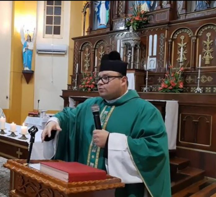 #Pracegover Foto: na imagem há um homem com microfone na mão, imagens de santo, um altar e a bíblia